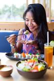Young adult girl enjoying sushi