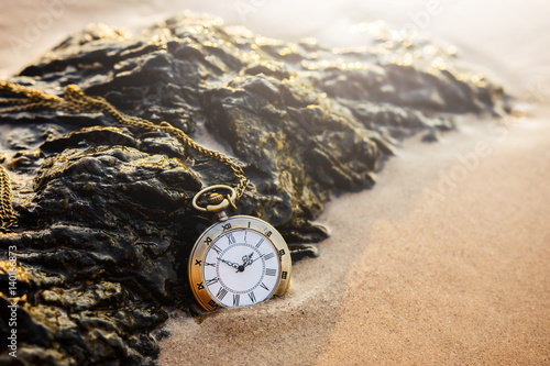 Vintage pocket watch on golden sand beach Poster