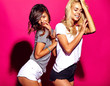 fashion portrait of smiling brunette and blond models in summer casual clothes on colorful pink background
