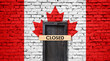 Canada flag on brick wall with closed door and Closed sign