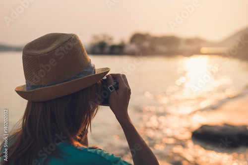 Young woman traveller taking photo on the beach at beautiful sunset