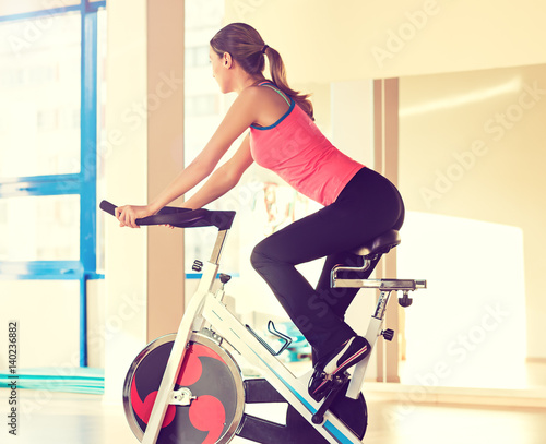 Young athletic woman in sports training rides on the bike.Active girl doing sport biking. Sport life.