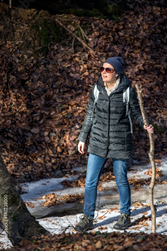 Woman with sunglasses hike through the woods at the beginning of spring Poster