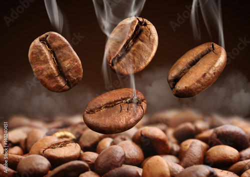 Closeup falling coffee bean with steam on brown background