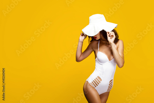 Portrait of young model posing against of yellow background in white hat and body. Isolated