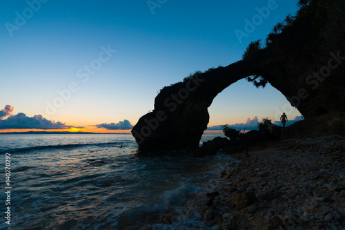 Plagát Silhouette of Natural Bridge at Sunset on Rocky Beach on Neil Island of the Anda