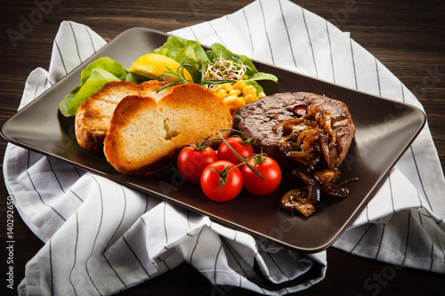 Fotobehang Koken Grilled steak with toasted buns on wooden background