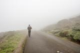 Lone man walking through the white fog - 140294234