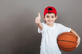 Cheerful little boy holding basketball ball and showing thumbs up