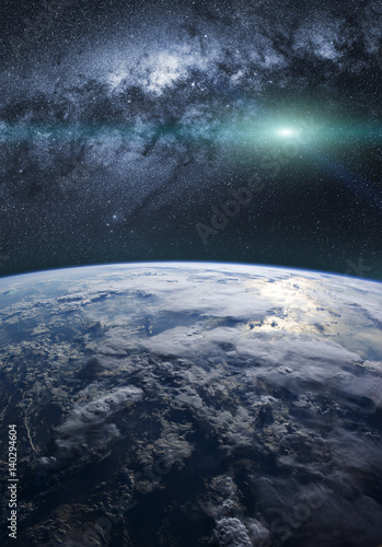A fantasy view of the planet Earth with the milky way in background, and shiny stars in the sky. Elements of this image furnished by NASA.