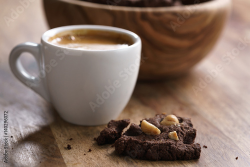 Poster cup of fresh espresso with homemade chocolate cookie with hazelnuts, shallow foc