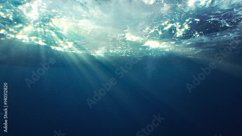 Fotobehang Koraalriffen Beautiful underwater sea scene view with natural light rays, shining through the water's glittering and moving surface, caustics, bubbles, and foam, perfect for background and digital composition