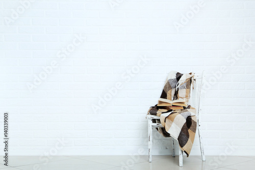 Poster Wooden chair with plaid and books on a brick wall background