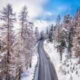 Asphalt curved road leading to high snowy mountains behind fog, winter season