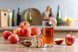 Glass of apple juice and ripe pink apples on a kitchen table