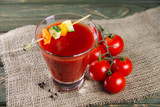 Tomato juice with vegetable decorations on a wooden background