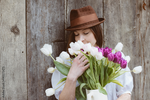 Cute brunette female with bunch of tulip flowers, easter concept