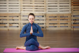 Young attractive woman practicing yoga, exercise, Lotus pose, namaste, working out, wearing sportswear.