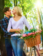 Walking bike of couple in park and kissing. Summer friends walk outdoor. First date of two young people in good weather day.