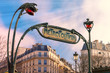 Traditional Art Nouveau entrance sign for the Metropolitan and red streetlights, typical Parisian buildings in the background, Paris, France