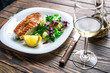 Lovely fish steak with salad, lemon and white wine on a wooden table