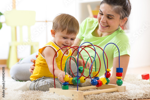 Kid boy plays with educational toy in nursery at home. Happy mother looking at her smart son.