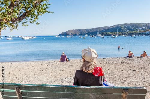 femme assise sur un banc, plage de Cadaqués, Costa Brava, Espagne