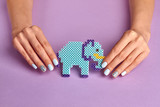 Blue toy elephant and female manicure on a violet background.