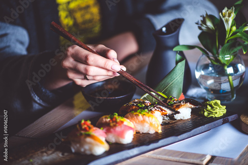 Man eating sushi set with chopsticks on restaurant Poster