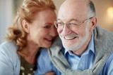Portrait of loving senior couple sitting close together cuddling caringly and smiling At home, focus on elderly man wearing glasses