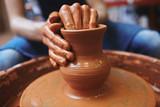 Human hands making curves of rotating clay jug