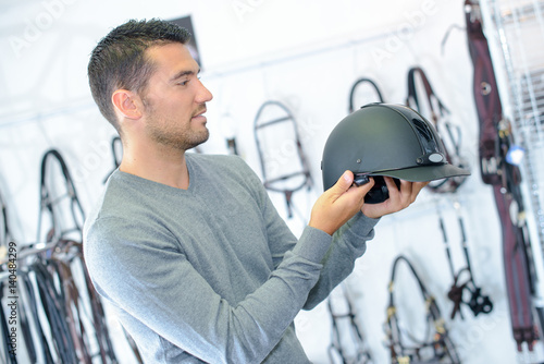 Man in equestrian shop holding riding hat