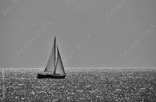 minimalistic black and white photo of a sailing boat on a sunny day - 140495897