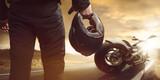 Motocyklista stojący z motocyklem na drodze