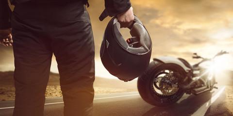 Motorradfahrer steht mit Motorrad auf einer Straße