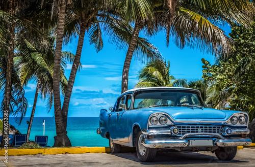 Blauer amerikanischer Oldtimer parkt am Strand unter Palmen in Varadero Kuba - S Poster