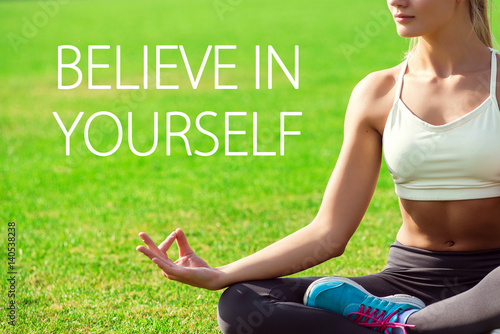 Young woman meditates while practicing yoga. Freedom concept. Motivation text believe in yourself Photo by dmshpak