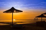 Sunrise at the sea with silhouette of beach umbrellas