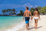 Summer vacation suntan couple holding hands having fun on hawaii beach destination. People walking together relaxing under the sun.
