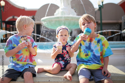 Fotografiet Three Young Children Eating Ice Cream by Fountain on Summer Day
