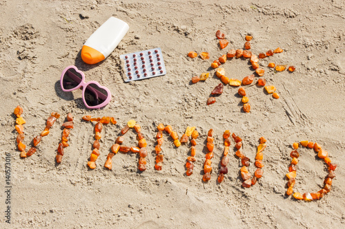 Foto Murales Medical pills, inscription vitamin D and accessories for sunbathing on sand at beach, summer time and healthy lifestyle