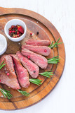 Roasted beef steak cut into slices with rosemary on wooden cutting board