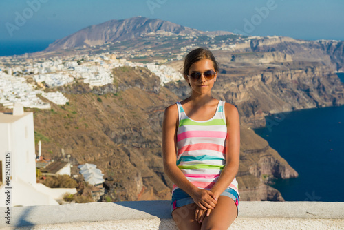 Cheerful girl  to the islands of Greece, Girl in glasses, Girl tourist in bright summer clothes. Young woman tourist posing  the most romantic island - Santorini. concept of  tourism and travel,