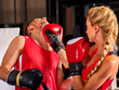 Boxing workout woman in fitness class. Sport box exercise two people. Man trainer holding sport mitts on ring. Female boxing gloves are red. Close up of female muscular back.