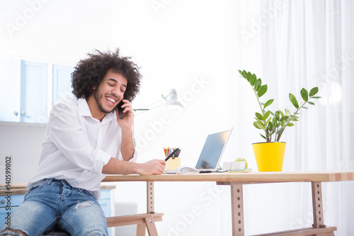 Handsome hipster freelance man talking over mobile or smart phone while working at home. Happy man smiling while talking with friends or business partners.