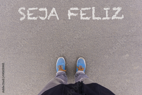 Poster Seja feliz, Portuguese text for Be Happy text on asphalt ground, feet and shoes