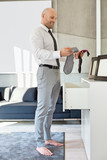 Fototapety Full length side view of businessman selecting socks at home