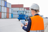 Fototapety Rear view of female engineer using tablet PC in shipping yard