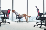 Fototapety Full length side view of young businesswoman leaning back in chair at office