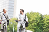 Fototapety Businessmen talking while riding bicycles outdoors